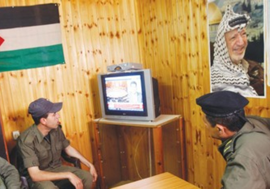 Palestinian security officers watch TV