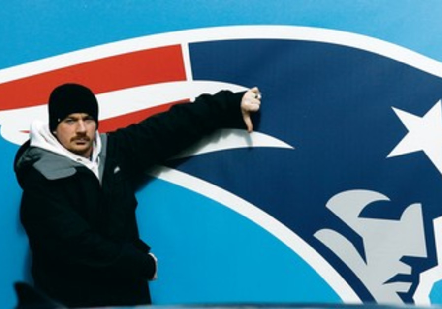 FAN poses in front of a New England Patriots logo