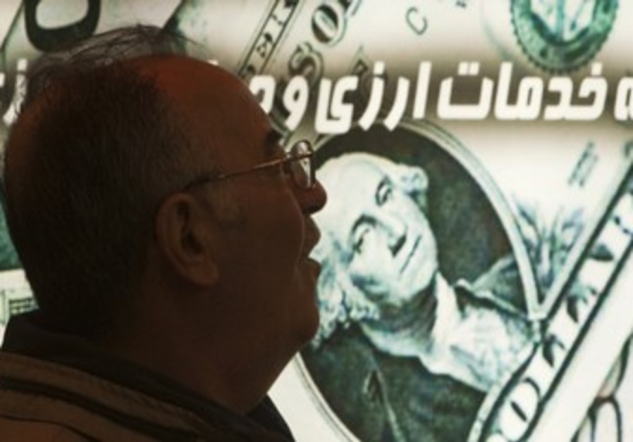 Iranian man walks past a currency exchange shop