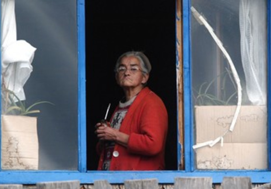 Elderly woman looks out of window [illustrative]