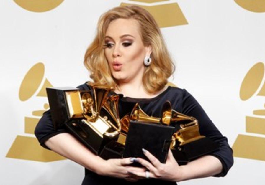 Singer Adele holds her 6 Grammy awards.