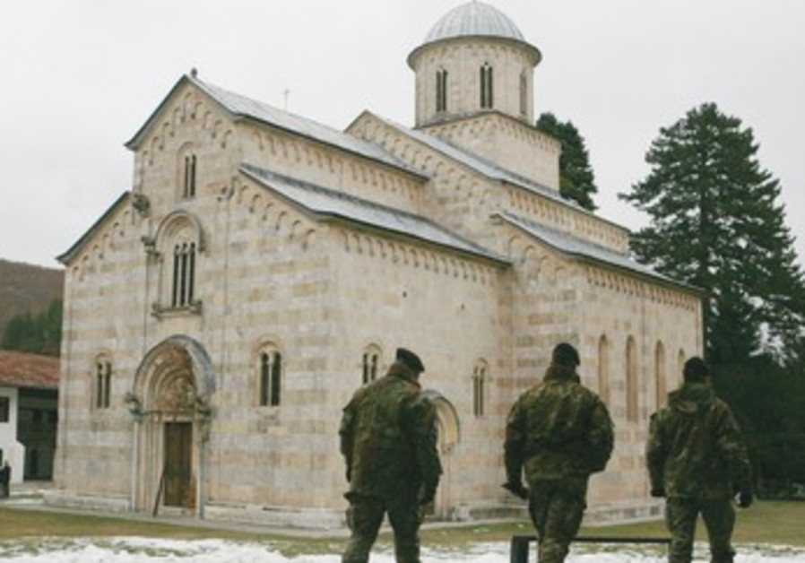 Kosovo Force soldiers walk pass a monastery in Dec