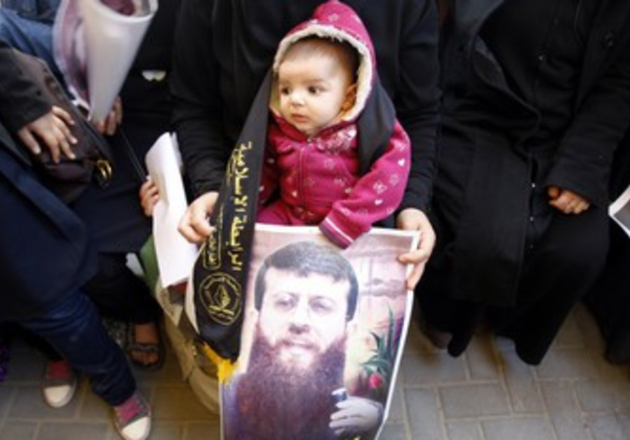 Child holds picture of Khader Adnan