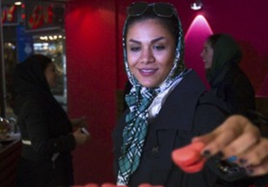 An Iranian woman takes a Valentine's Day cookie at
