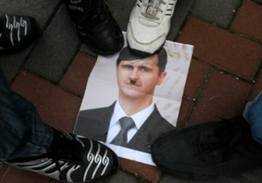 Arab Israelis step on photo of Assad as Hitler.
