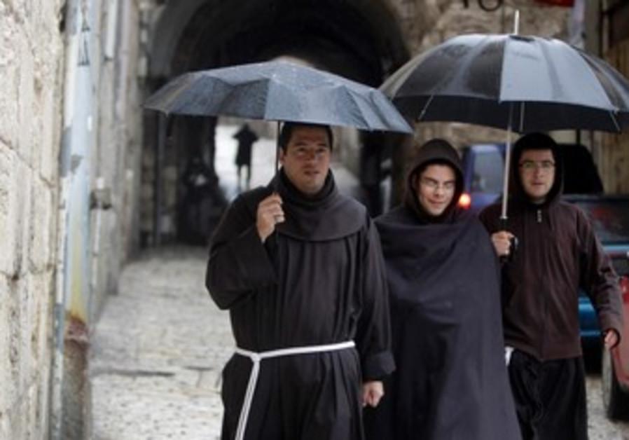 Monks walk in rain in J'lem's Old City