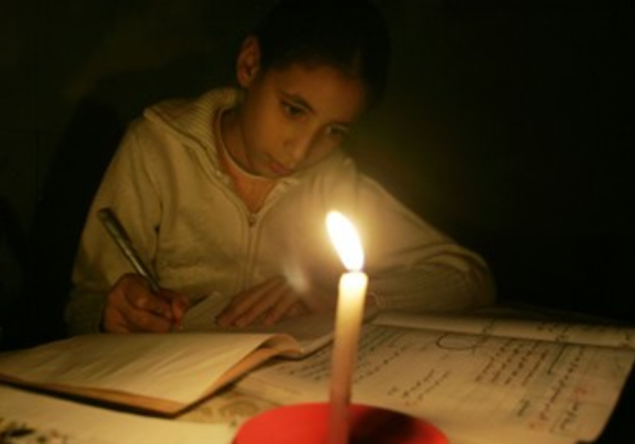 Palestinian girl studies by candle light in Gaza