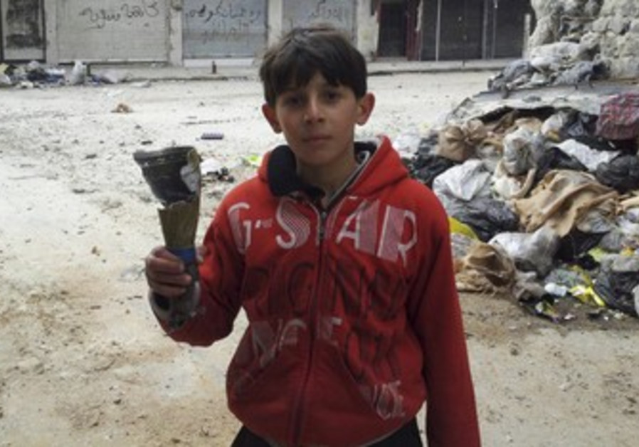 Boys hold remains of mortar in Homs neighorhood