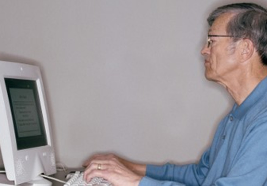An elderly man at a computer. [illustrative]