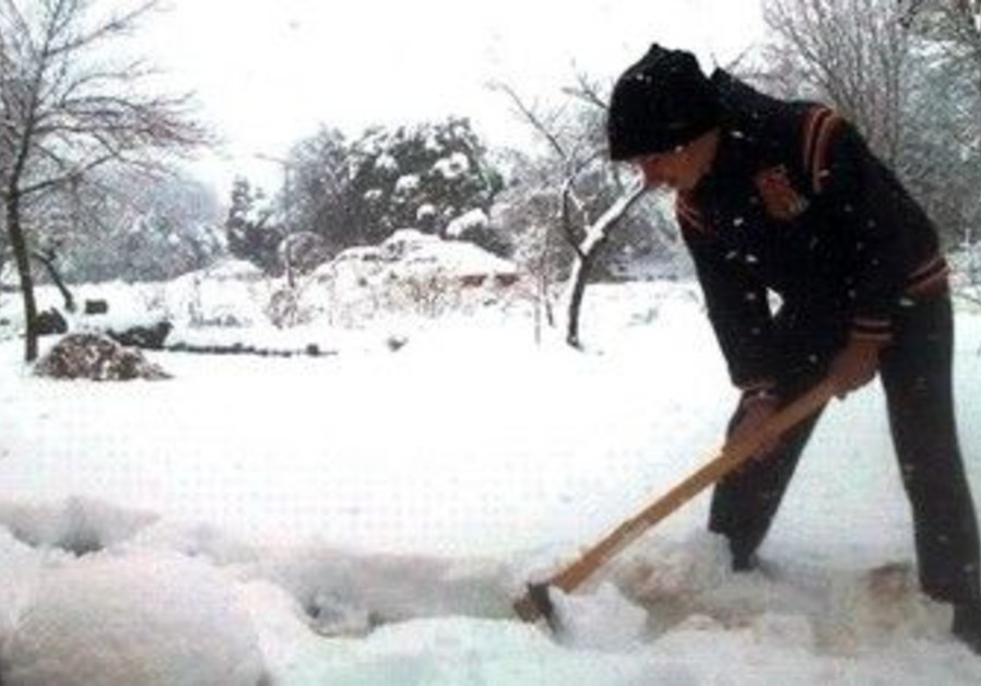 Kibbutz Maron Golan resident digs through snow