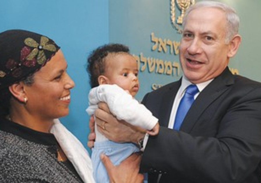 PM holds Ethiopian baby at Knesset