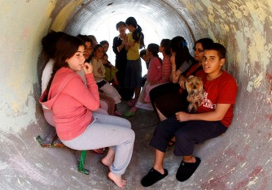 Children take shelter from rockets in sewage pipe