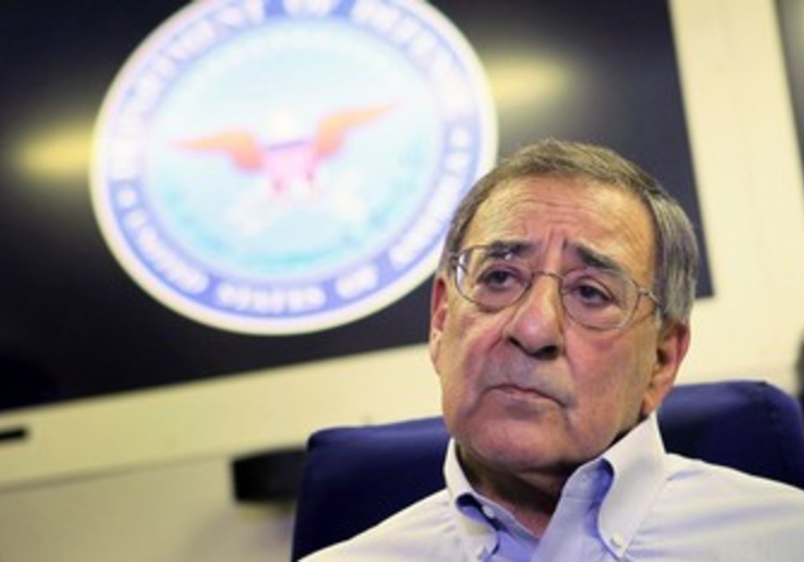 Leon Panetta speaks with reporters on a plane