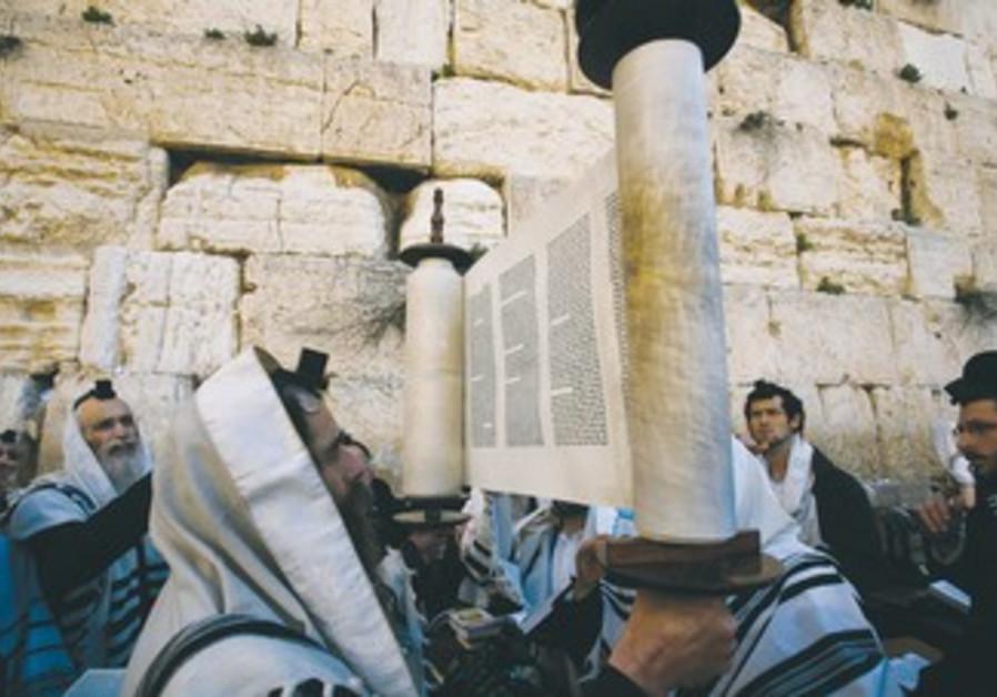 A worshiper holds up a Torah scroll