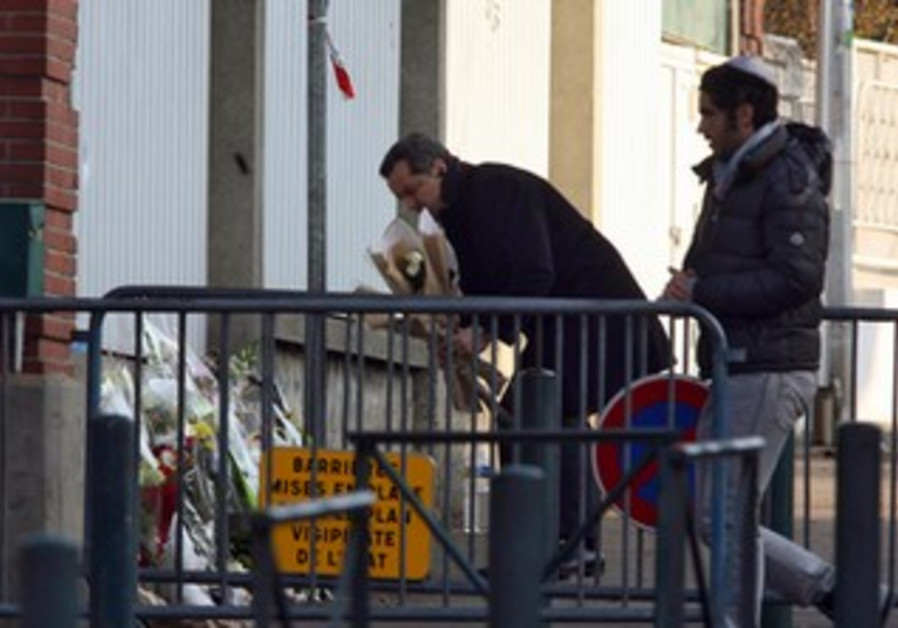 People lay flowers outside Ozar Hatorah, Toulouse