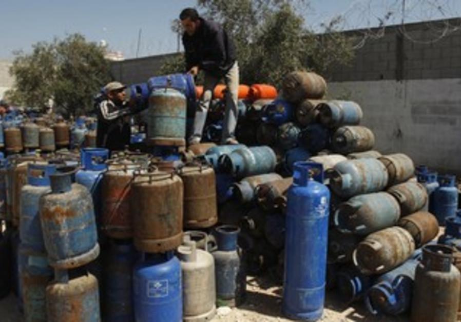 Gazans arrange gas cylinders at gas station
