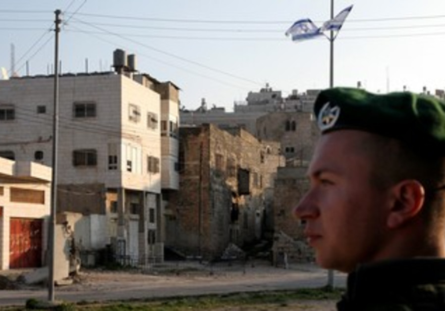 IDF soldier stands guard near Beit Hamachpela