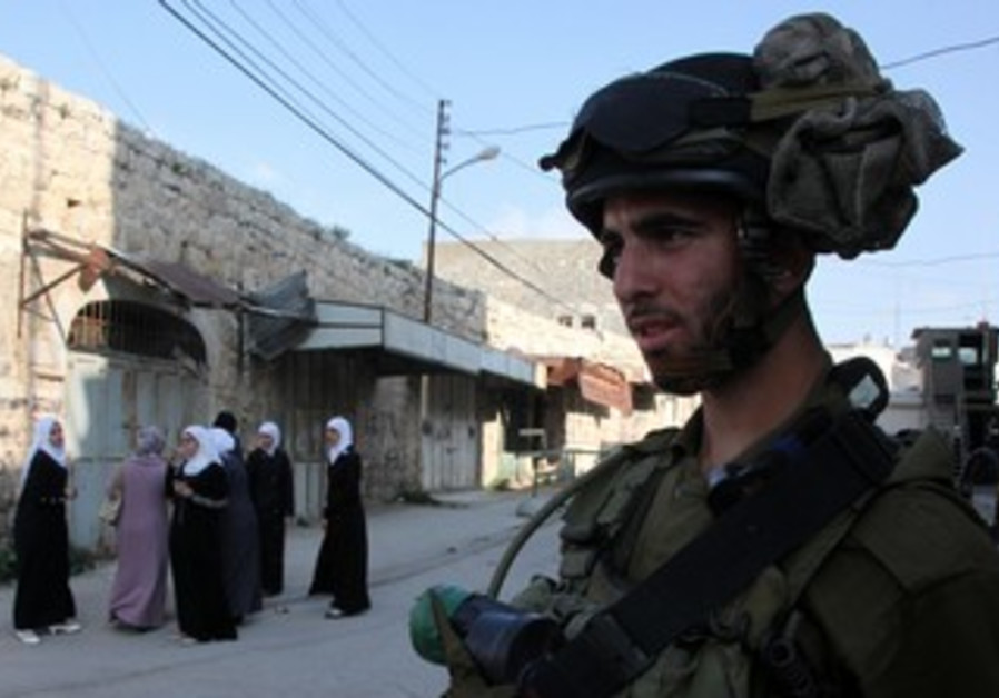 Soldier, Arab women in Hebron