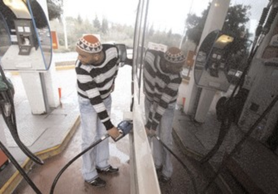 A man pumping gasoline at a gas station