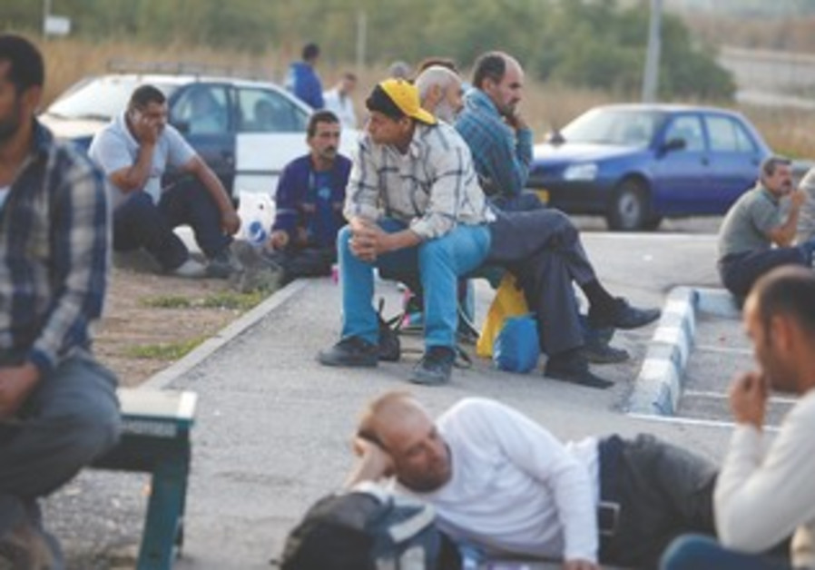 Palestinian labourers wait for work