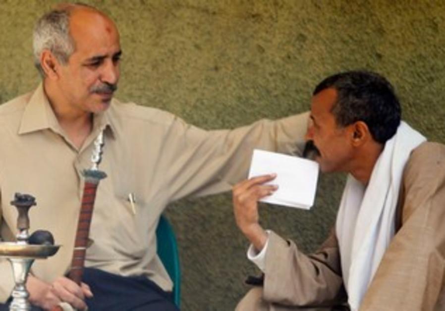 Egyptian men talk and smoke shisha.
