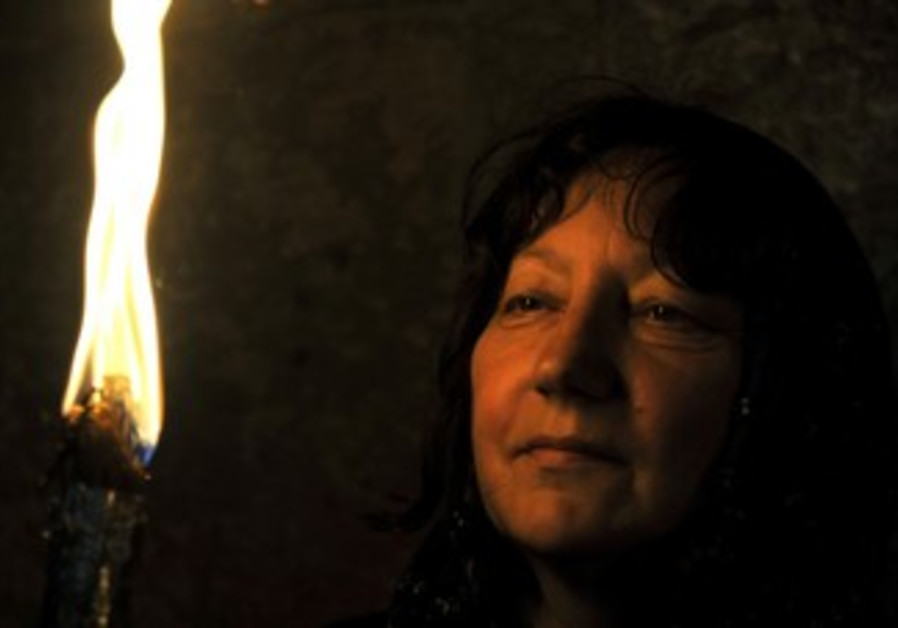 Woman gazes at Holy Fire on Holy Saturday