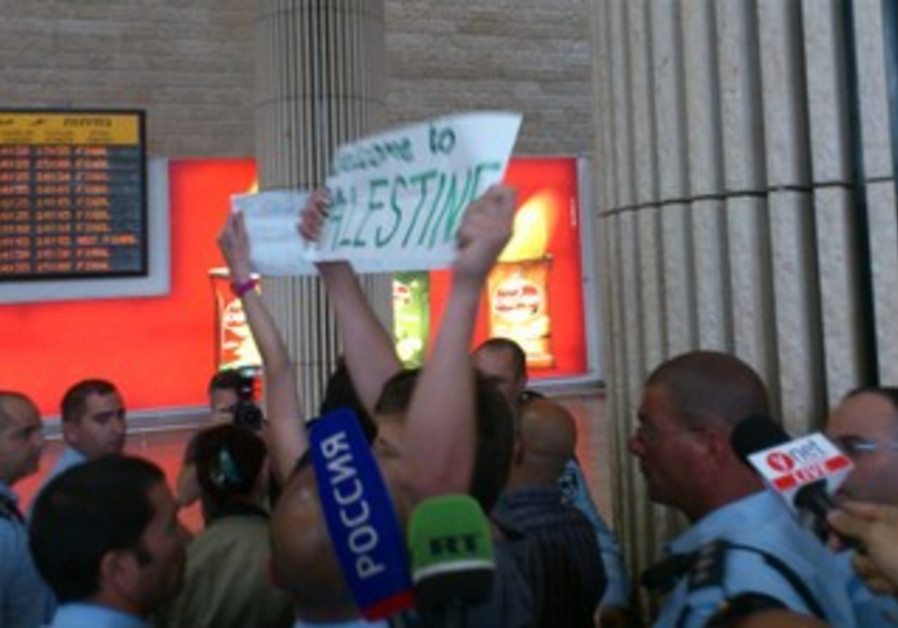 Activists hold up welcome to Palestine signs