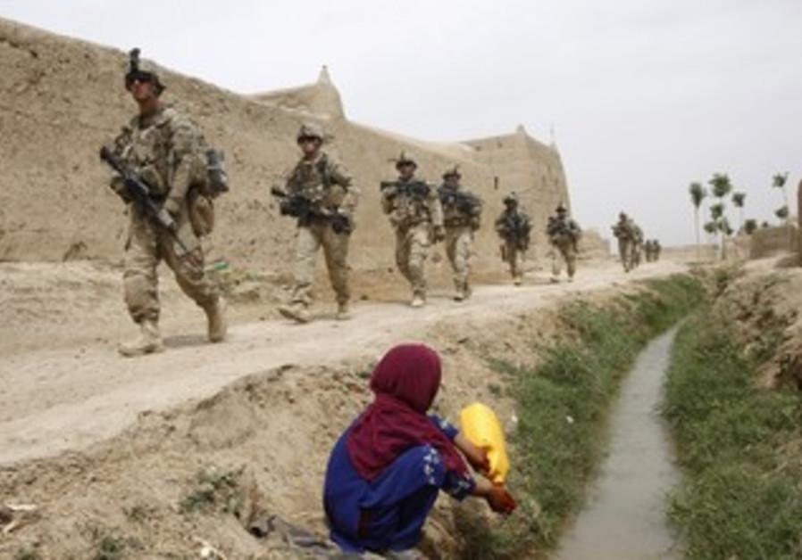 Afgan girl watches US soldiers walk past