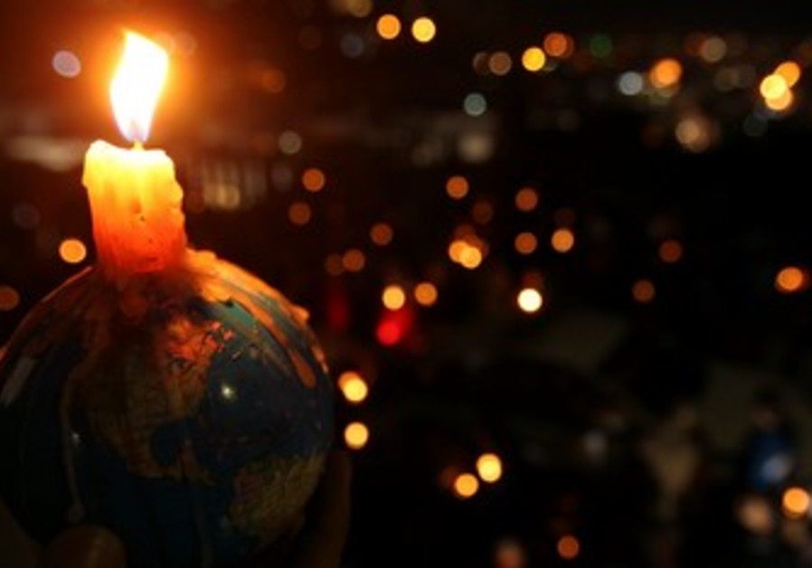 People hold candles during Earth Hour
