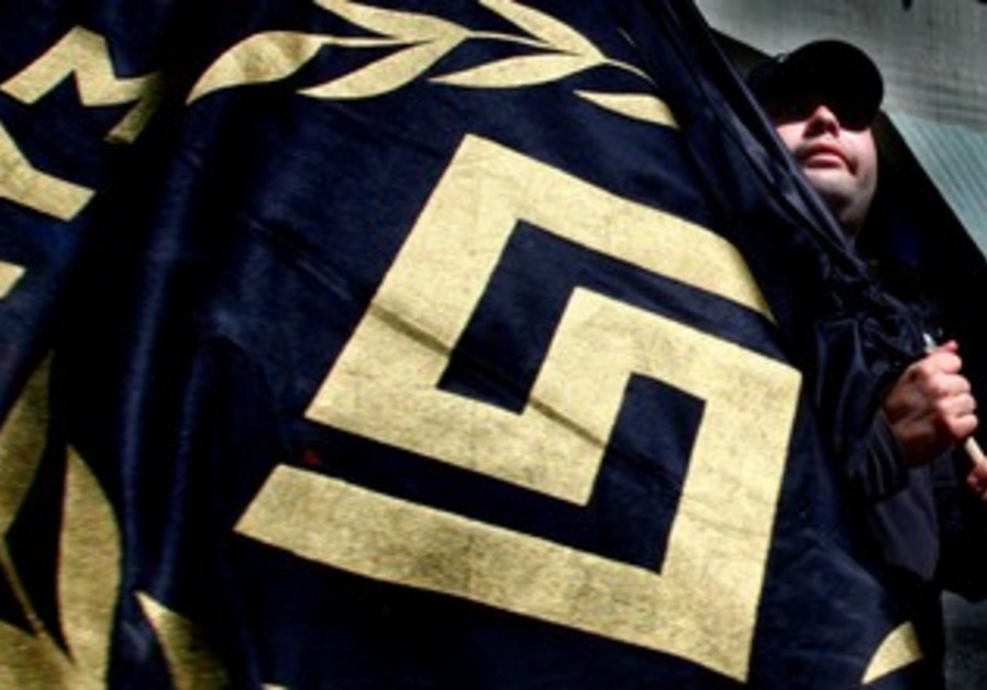 Golden Dawn party activist waves flag with logo
