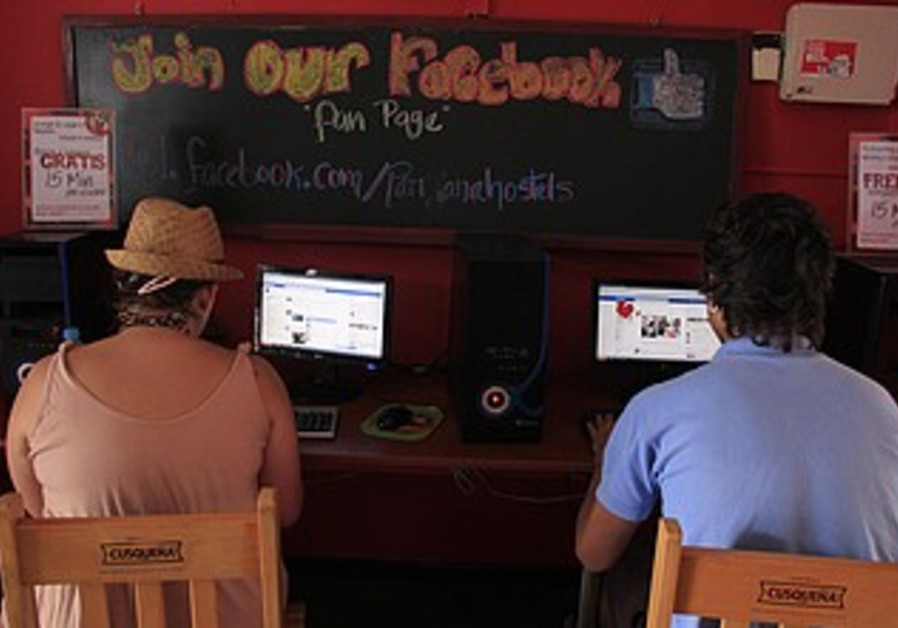 Travellers use Facebook at a Lima hostel