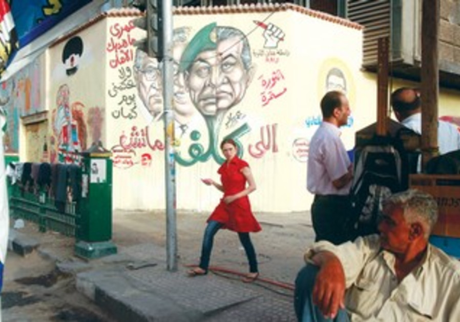 EGYPTIAN girl passes by graffiti