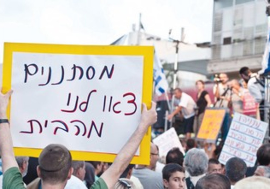 sign reads 'Infiltrators, leave our home.'