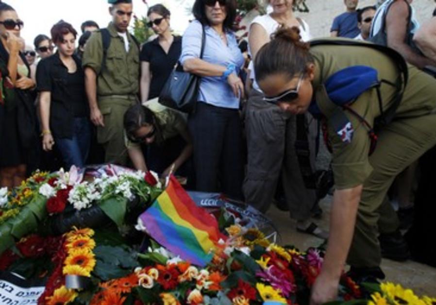 Mourners gather around the grave of Nir Katz