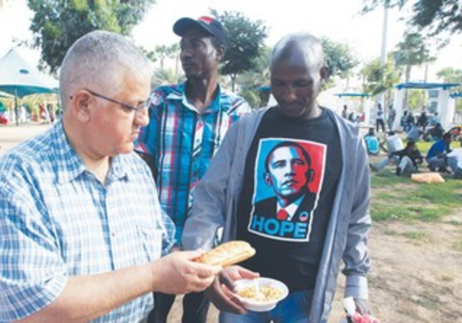 A VOLUNTEER hands out food to African migrants