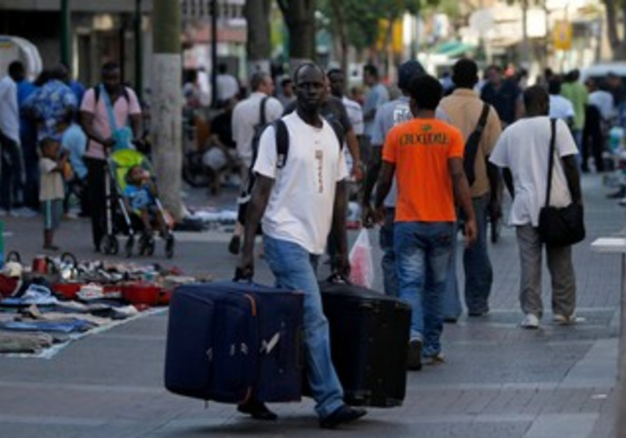 African migrant walks with suitcase in south TA