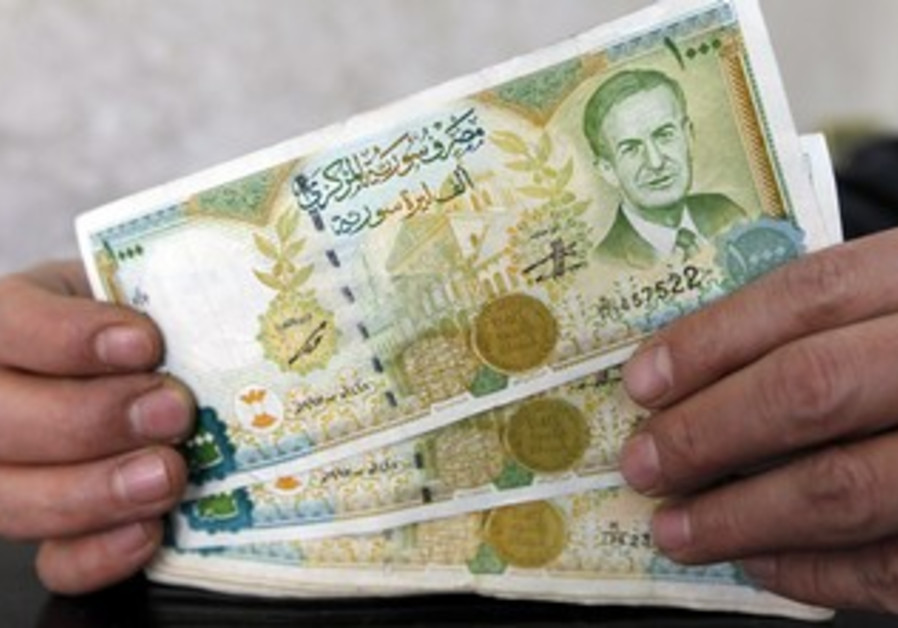 A money changer displays Syrian pounds