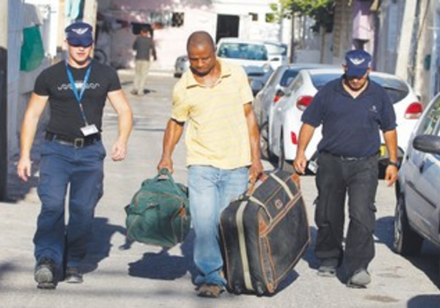 Immigration officers escort African migrant in TA