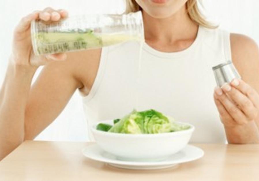 Woman pours salad dressing