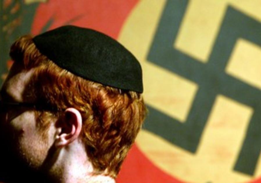 Jewish man in front of swastika at Shoah memorial