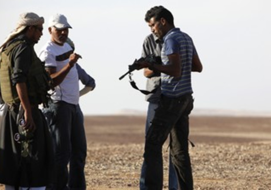 Beduins inspect their weapons in Sinai Peninsula