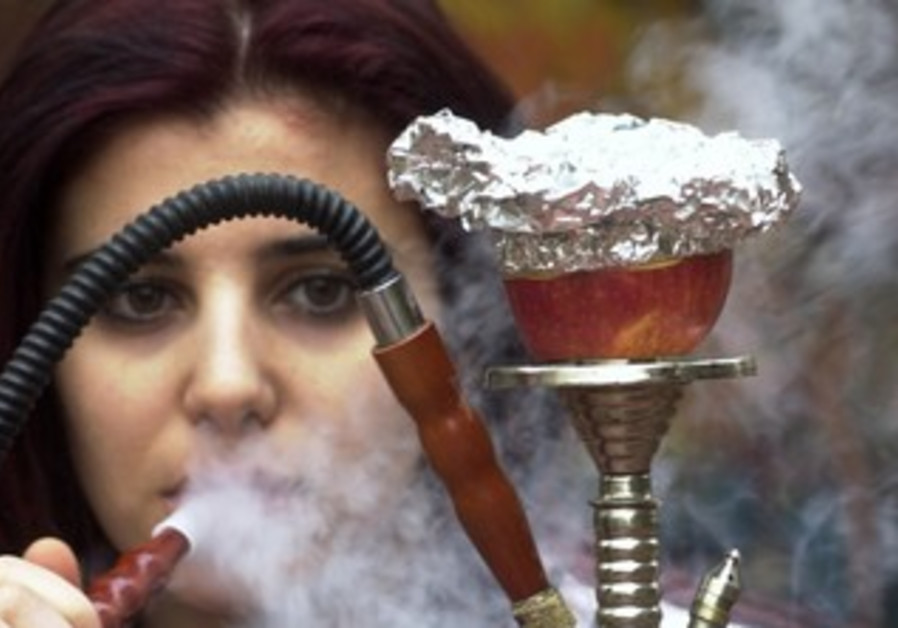 Woman smokes nargila from a hookah