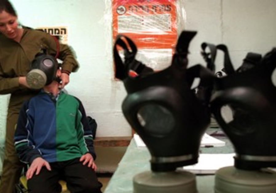 IDF soldier fits child with gas mask
