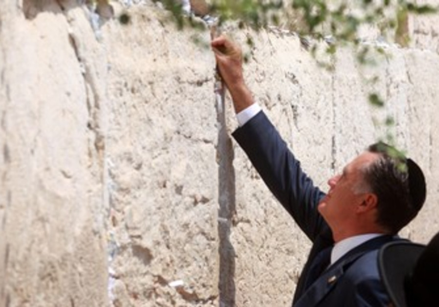Mitt Romney puts a note in the Western Wall.