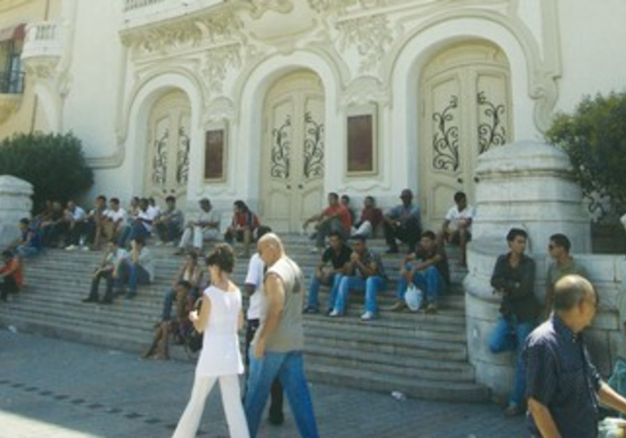 Tunisians sit on the steps of the opera house