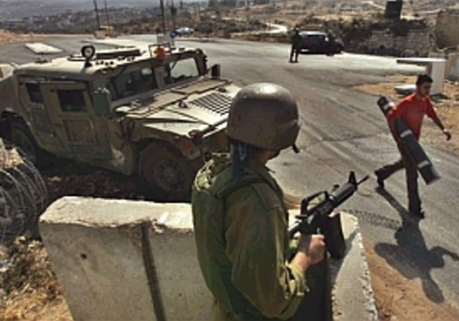 idf army checkpoint palestinian passes by 298