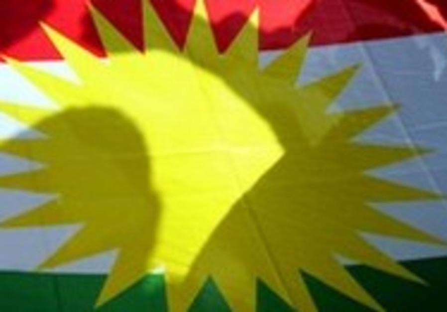 Kurds pose behind Kurdish flag