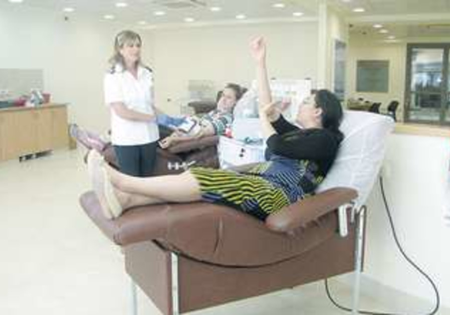 WOMEN DONATE blood at the Magen David Adom station