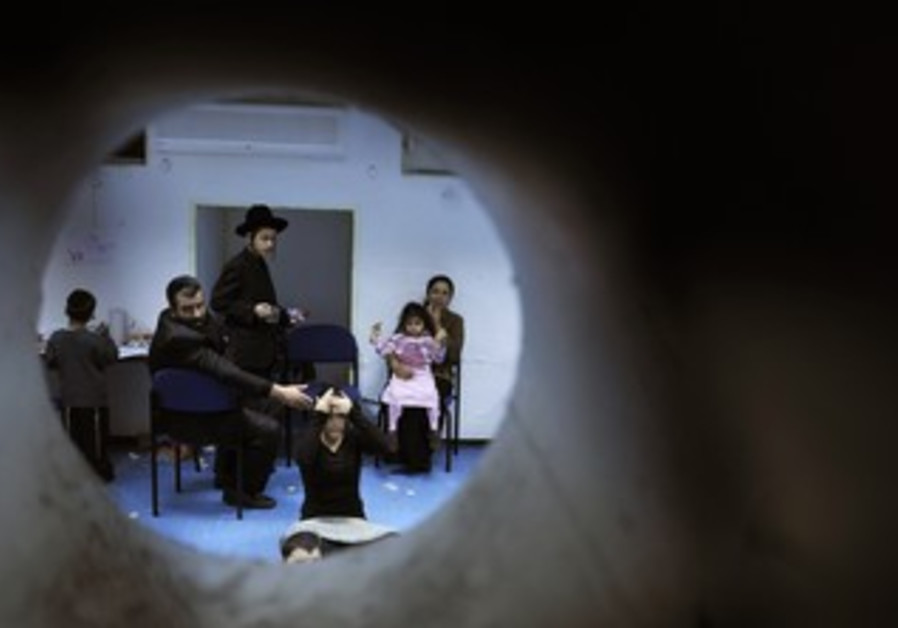 Israelis sit in a bomb shelter [illustrative photo