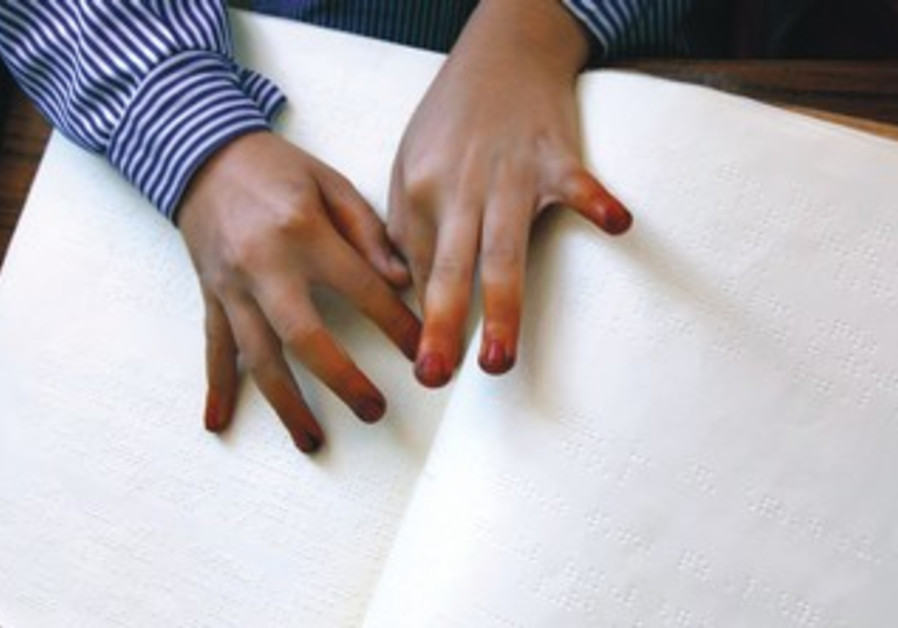 A BLIND pupil reads a braille book.